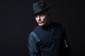 Retro 1900 modern fashion man. Wearing blue jeans shirt with gilet and trousers. Black hat. Studio shot against black.